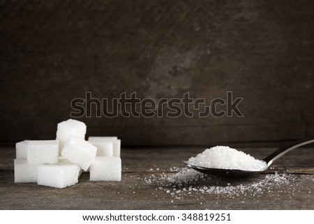 White sugar in silver spoon on wood table - stock photo