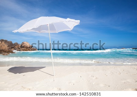 white sunshade at the tropical beach of La Digue, Seychelles, with granite rocks  and blue sky