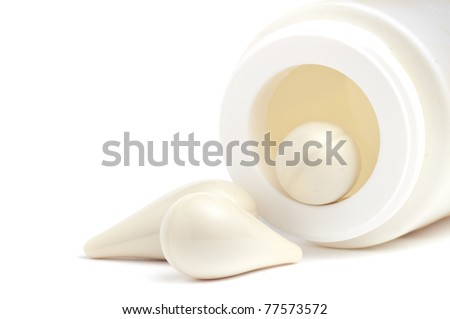 White suppositories in a bottle over white background - stock photo