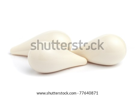 White suppositories on a white seamless background - stock photo