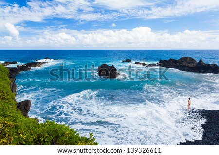 White surf in a tropical cove, girl looking out - stock photo