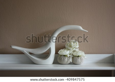 white swan statuette and flowers on white table in bright minimalism interior - stock photo