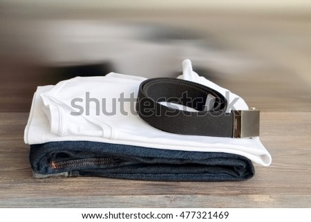 White T-shirt, blue denim jeans and cotton belt on a wooden board. Copy space. Wide panoramic image. Find more wide panoramas in our portfolio.
