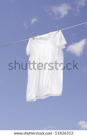 White t-shirt drying on outdoor clothesline