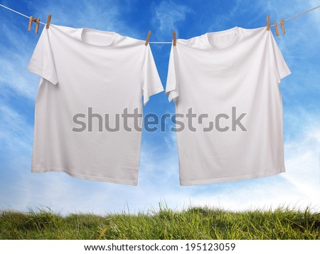 White t-shirt hanging on outdoor clothesline with blank front ready for logo or message - stock photo