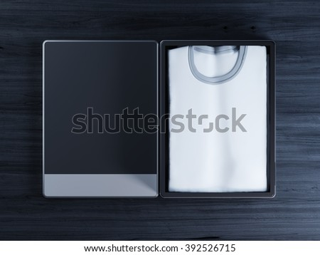 White T-shirt mockup in packing on a black wooden table. - stock photo