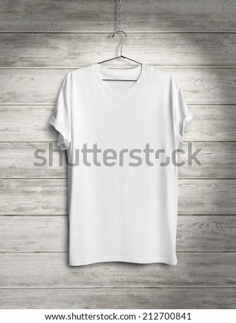 White t-shirt on wood wall with spotlight - stock photo