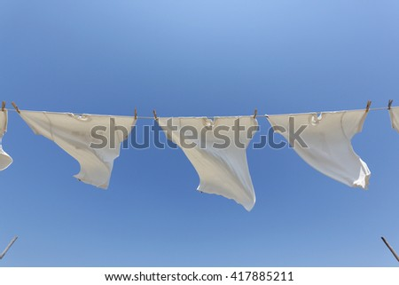 White t-shirts hanging on the clothesline against blue sky - stock photo