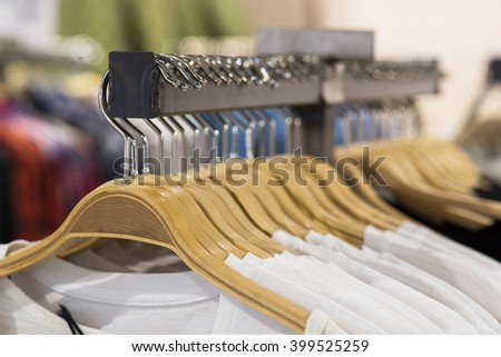 White t-shirts on hangers for sale in store - stock photo