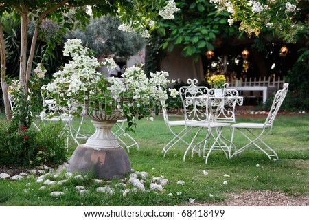 White table and chairs in beautiful garden. - stock photo