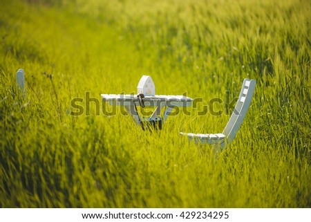 white table and chairs in green field