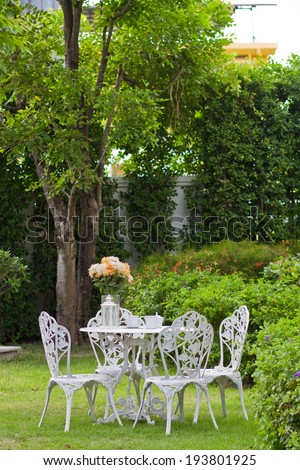 white table and chairs in the garden. - stock photo