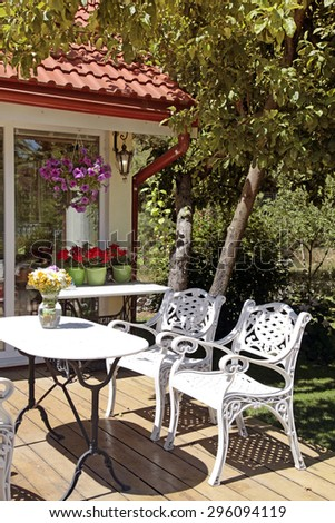 White table and chairs on wood patio in the garden
