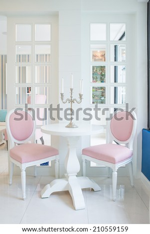 White table and pink chair with candle on table in living room - stock photo