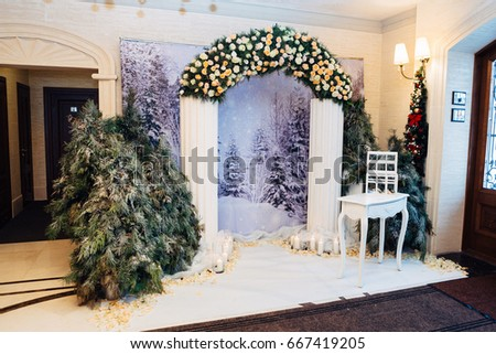 White table stands before wedding altar made of white columns and garland of roses