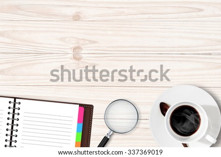 White table with coffee cup notebook Magnifying glass - stock photo