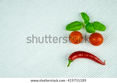 White table with red chilli, tomatoes and green basil - stock photo