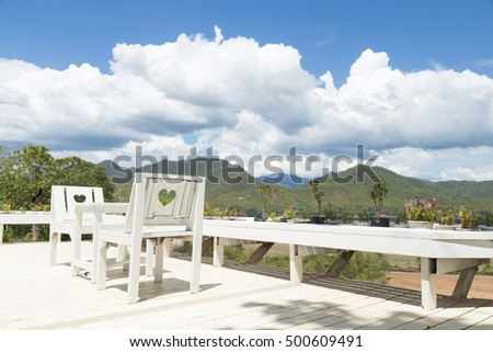 White tables and chairs on the balcony. The rear view of the mountains and the sky.