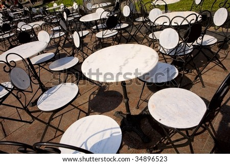 white tables and chairs under sun light - stock photo