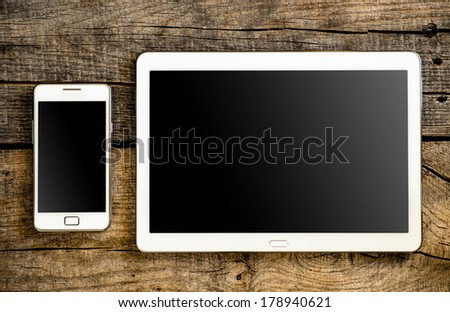 White Tablet and Smart phone. Mobile phone and Tablet pc on wooden table - stock photo