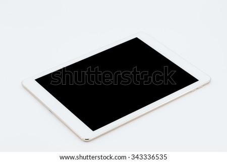 White tablet computer with blank screen mockup lies on the surface, isolated on white background. - stock photo