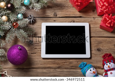 White tablet computer with branch Christmas tree and Christmas present on a wooden surface. Christmas background. Top view. Copy space. Free space for text - stock photo