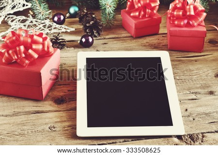 White tablet computer with Christmas gifts on wooden table closeup.Free space for text.  Copy space. Top view - stock photo