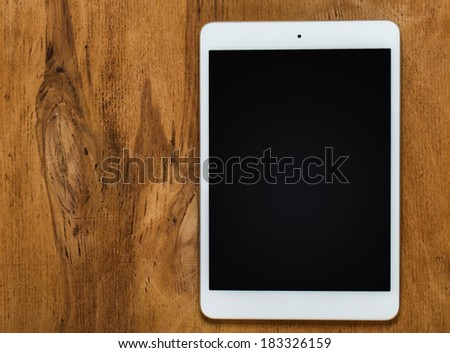 White tablet on the wooden table - stock photo