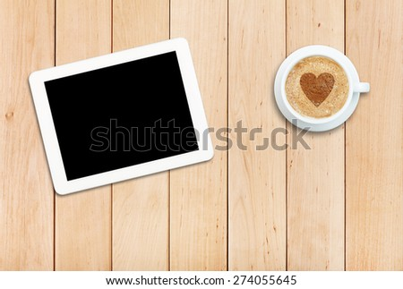 White tablet PC and coffee on a wooden table