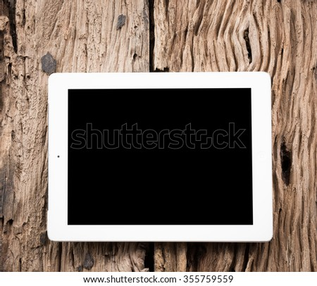 White Tablet pc on old wooden table - stock photo