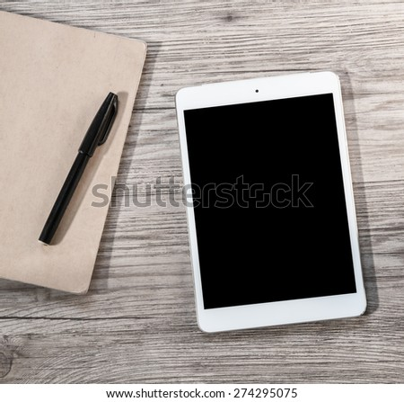 White Tablet with blank black screen and notebook with pen on the wooden background