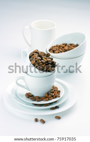 White tableware with roasted coffee beans on light background.