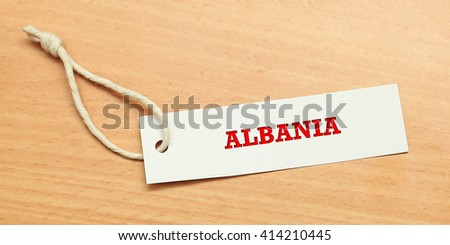 White tag on wooden background with word albania