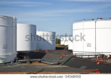 white tanks in tank farm with blue clear sky - stock photo