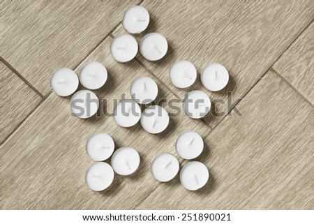 White tea lights in the shape of a star on wooden floor