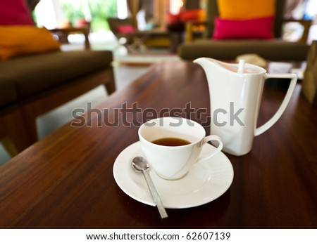 white tea pot and cup on the table - stock photo