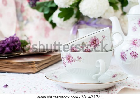 White tea set, a bouquet of lilac in a vase and a sprig of lilac in a cup