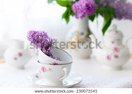 white tea set, a bouquet of lilac in a vase and a sprig of lilac in a cup. selective focus - stock photo