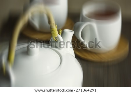 White teapot and two teacups with tea. Shallow DOF, Blur, Toning - stock photo