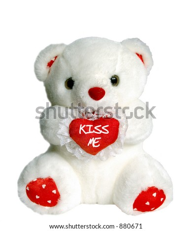 "White teddy bear holding heart pillow that says ""kiss me"""