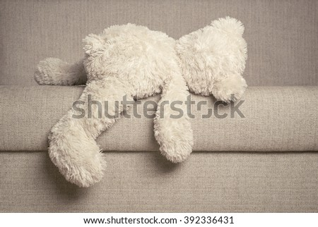 White Teddy bear is laying on edge of the sofa