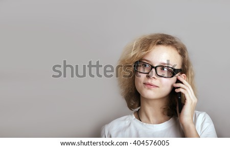 White Teenage girl wears glasses with curly hair talking on the phone