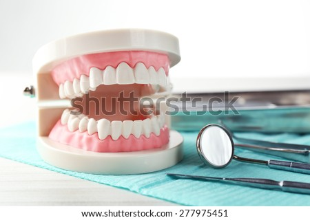 White teeth and dental instruments on table background - stock photo