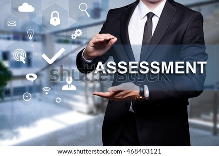 "White text with icon ""Assessment"" in the hands of a businessman. Business concept. Internet concept."