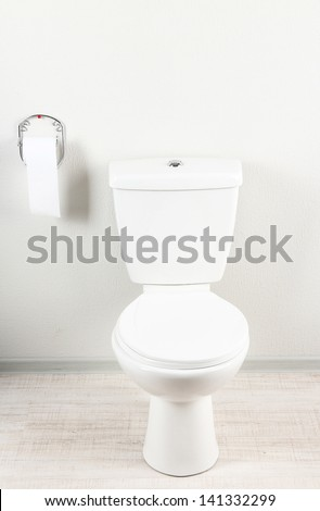 White toilet bowl and toilet paper in a bathroom - stock photo