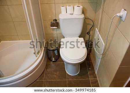 White toilet in it are three rolls of toilet paper near a shower is situated - stock photo