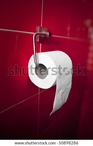 White toilet paper on red tiles background - stock photo