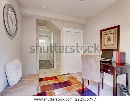 White tone office room with wooden desk and colorful rug