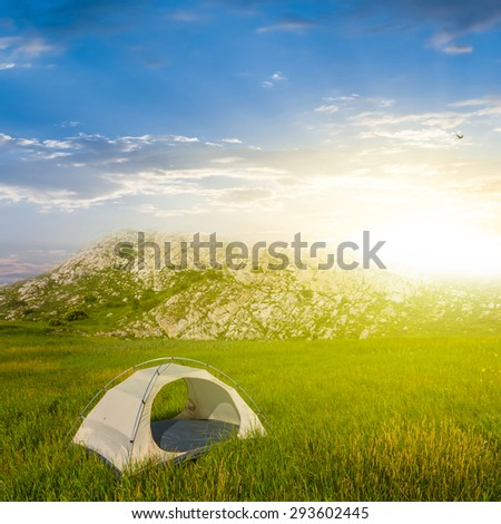 white touristic tent in a green hills at the sunrise - stock photo