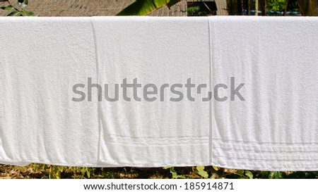white towel on clothesline in sunny day. - stock photo